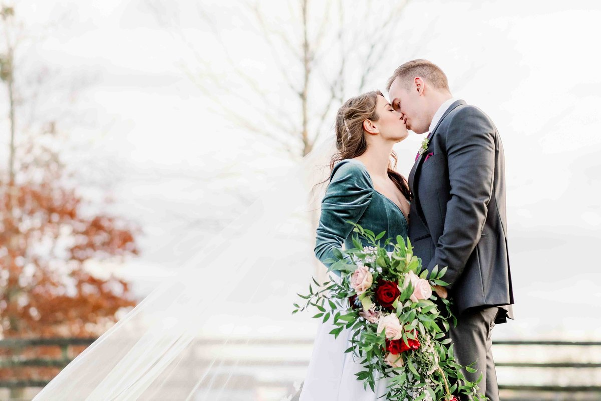 bride and groom share a kiss at the farm in northern virginia