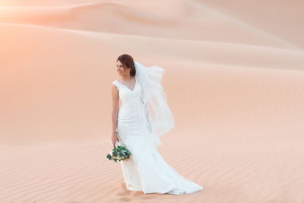 Bride in a lace wedding dress and a floral bouquet standing amidst Arabian desert dunes, elopement photoshoot organized by Lovely & Planned