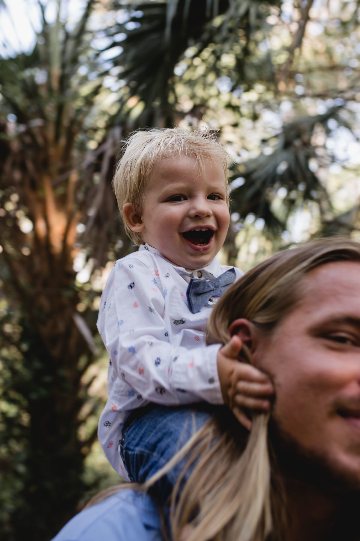 toddler on dad's shoulders laughing
