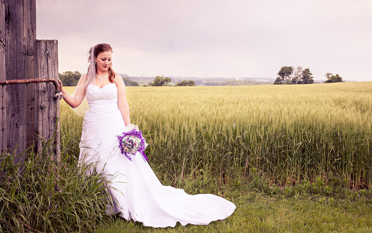 A bride in a field of wheat holds her colourful bouquet with her hand on a wooden railing.