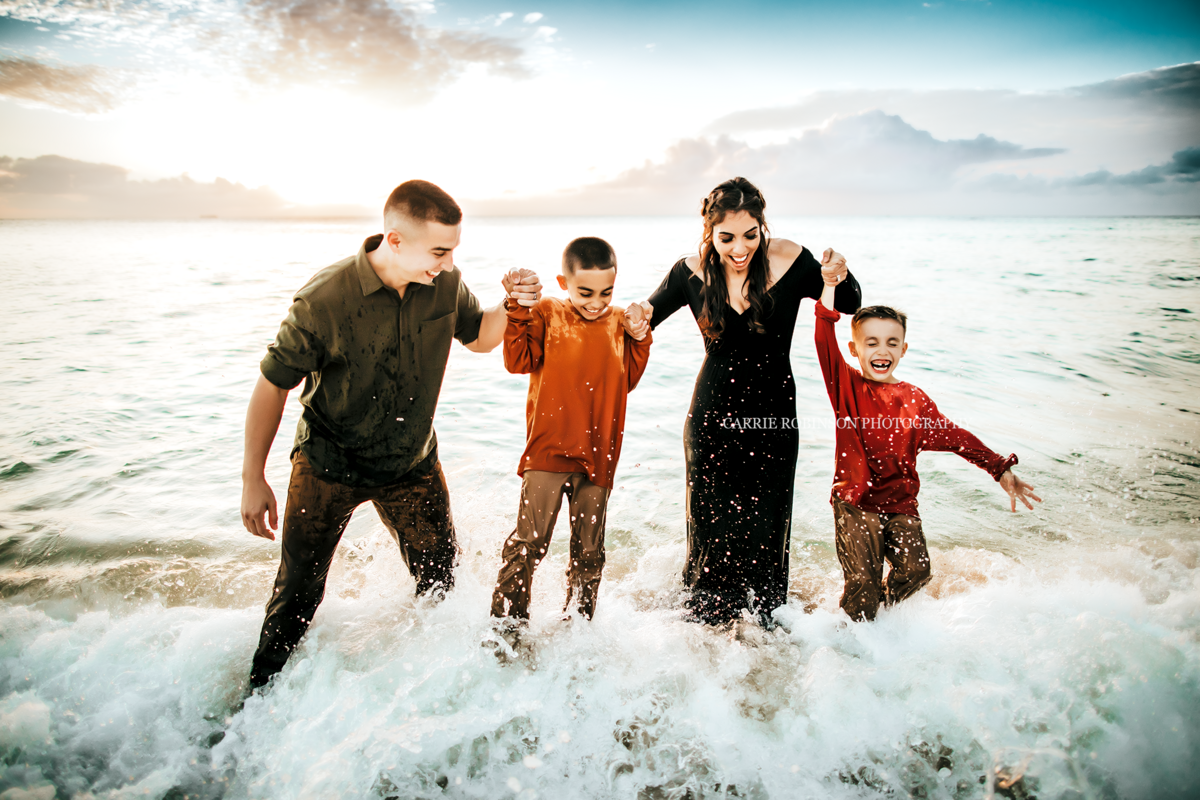 Okinawa Family Photographer family playing in water with waves crashing on family behind family