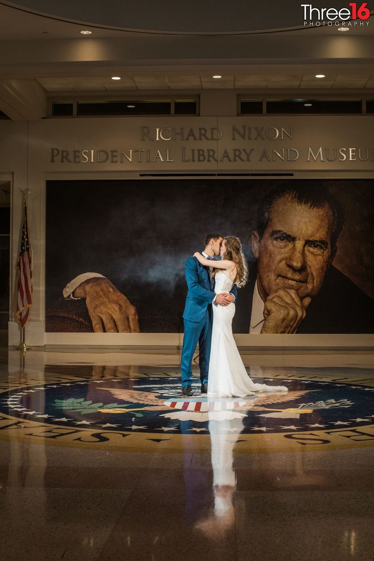 Bride and Groom kiss in the middle of the Richard Nixon Library lobby