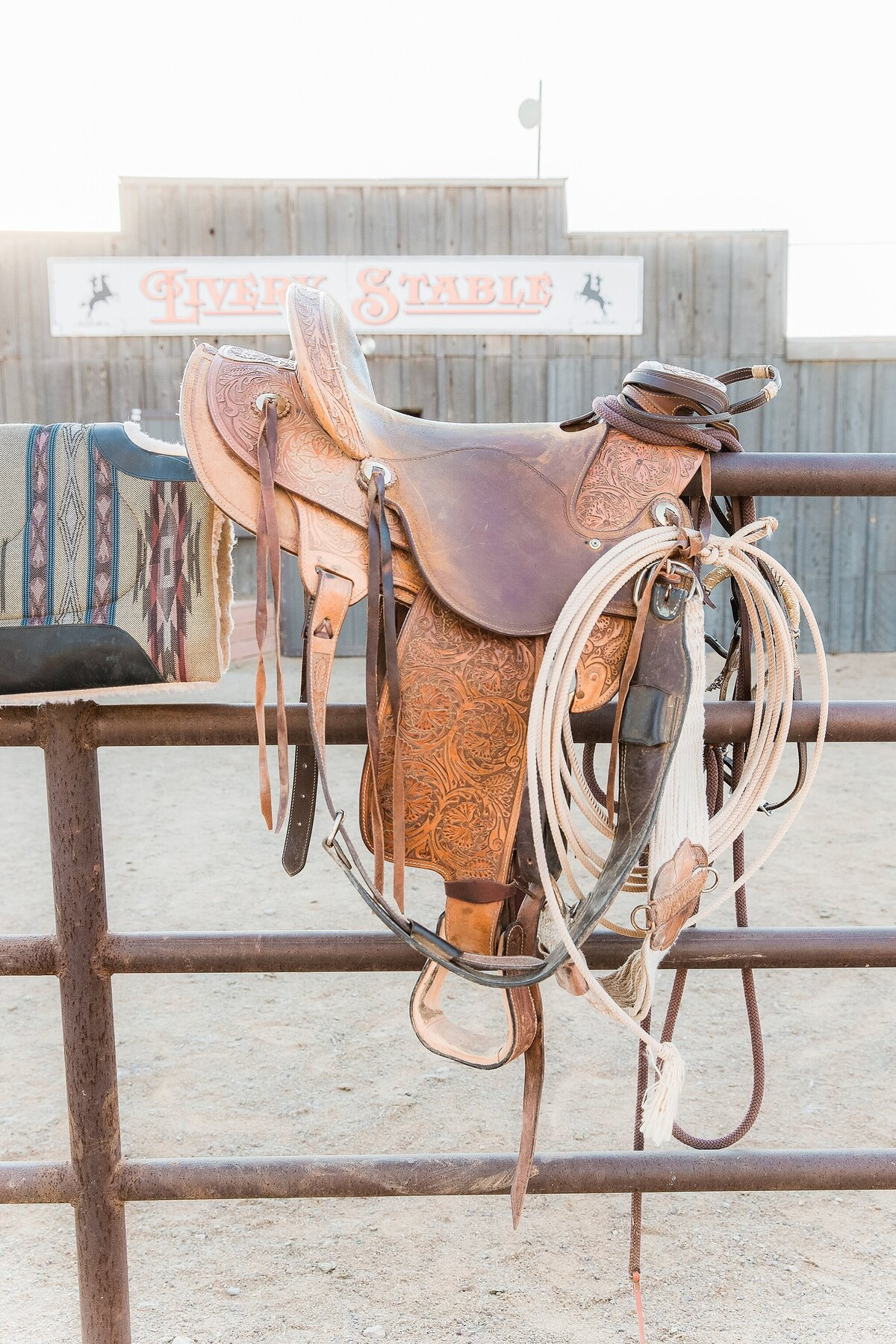 photo of a western saddle resting on a fence.