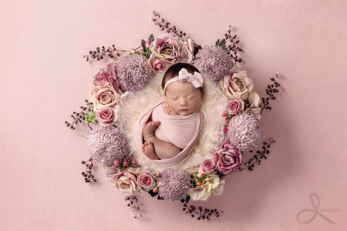 Baby girl in wreath of pink flowers