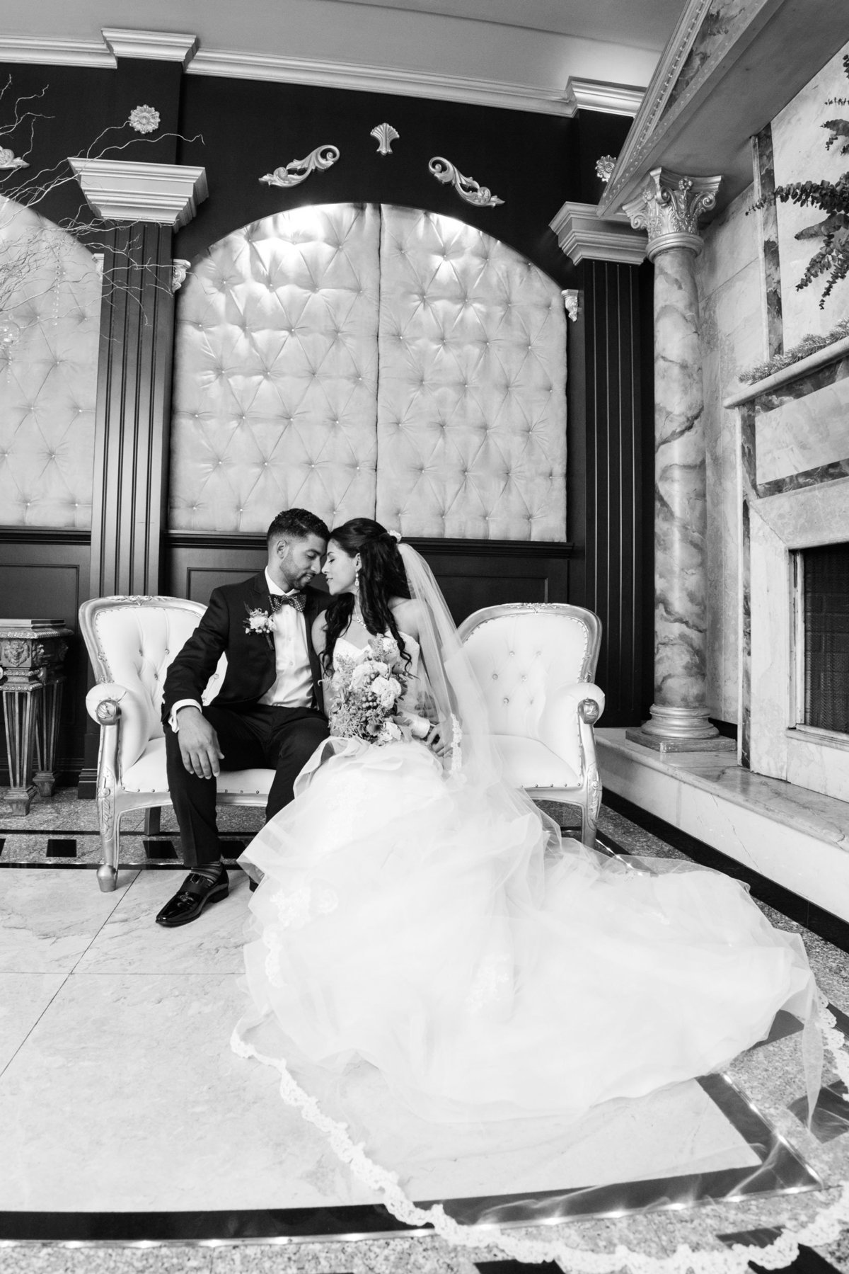 Black and white photo of bride and groom sitting on a sofa at The Sands