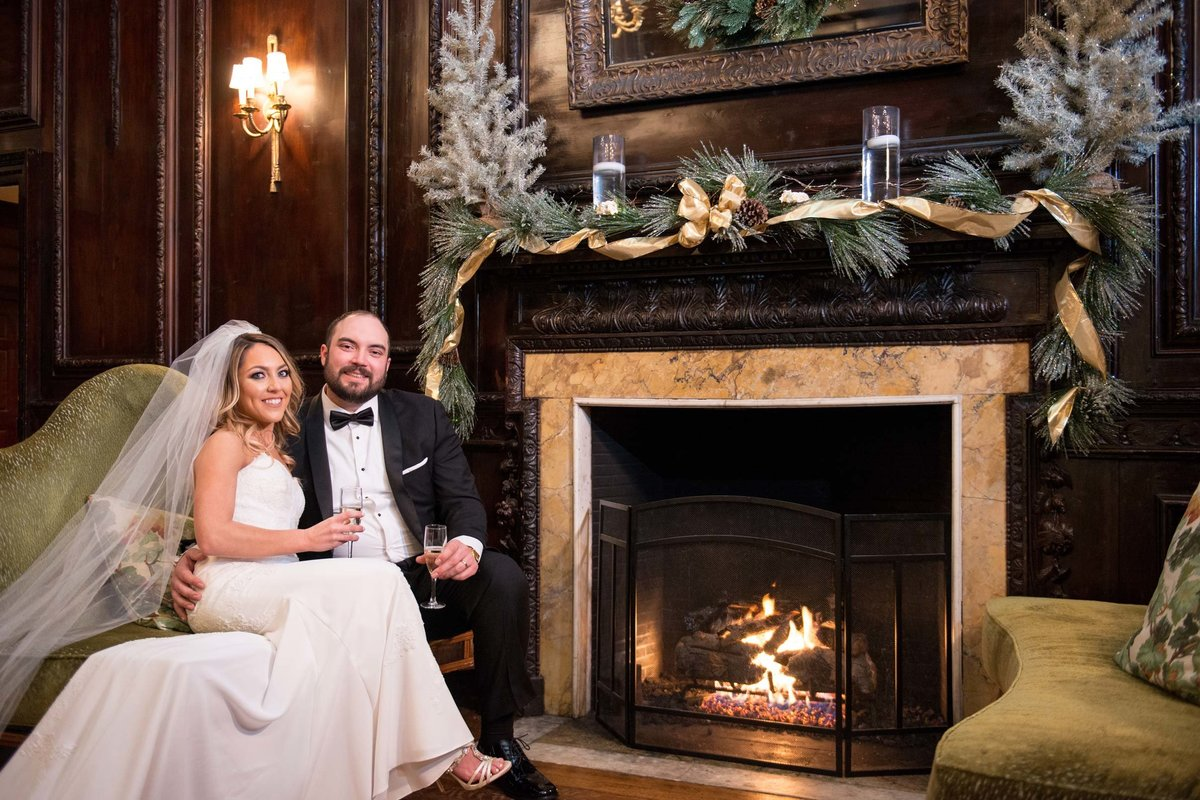 Bride and groom next to the fire place at The Mansion at Oyster Bay