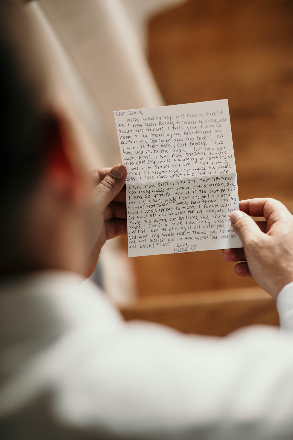 An image from behind of the groom reading the loving handwritten message from the bride before the wedding begins by Garry & Stacy Photography Co - Sarasota FL wedding photographers