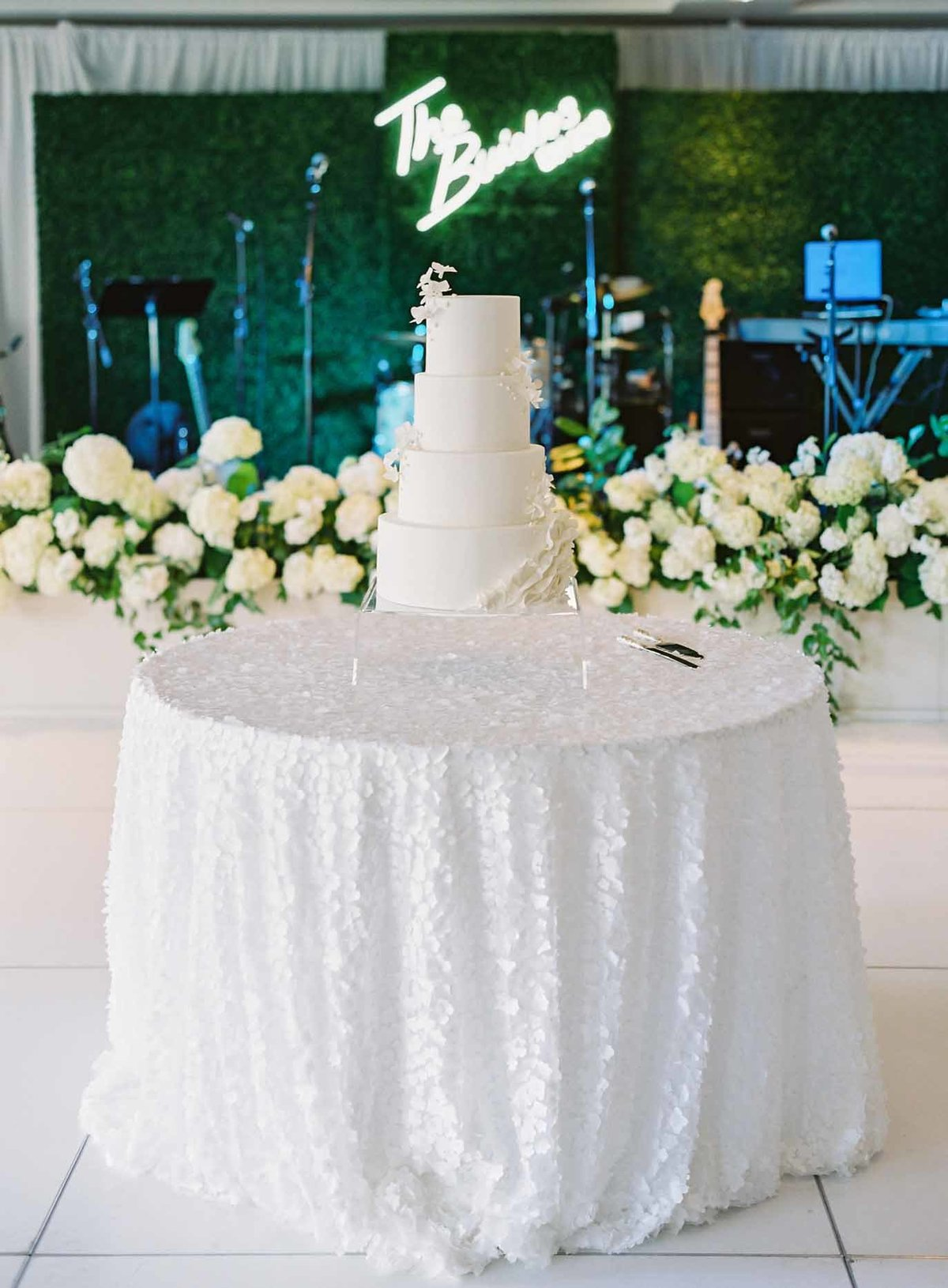 Stunning simple all white tiered wedding cake takes center stage on the dance floor in front of a hedge of white hydrangea.