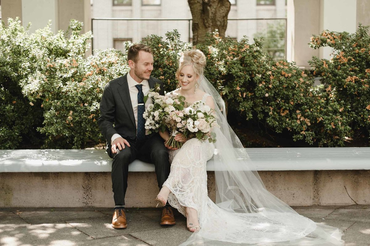 Lovely bride and groom sitting happily on a bench together in the sun.
