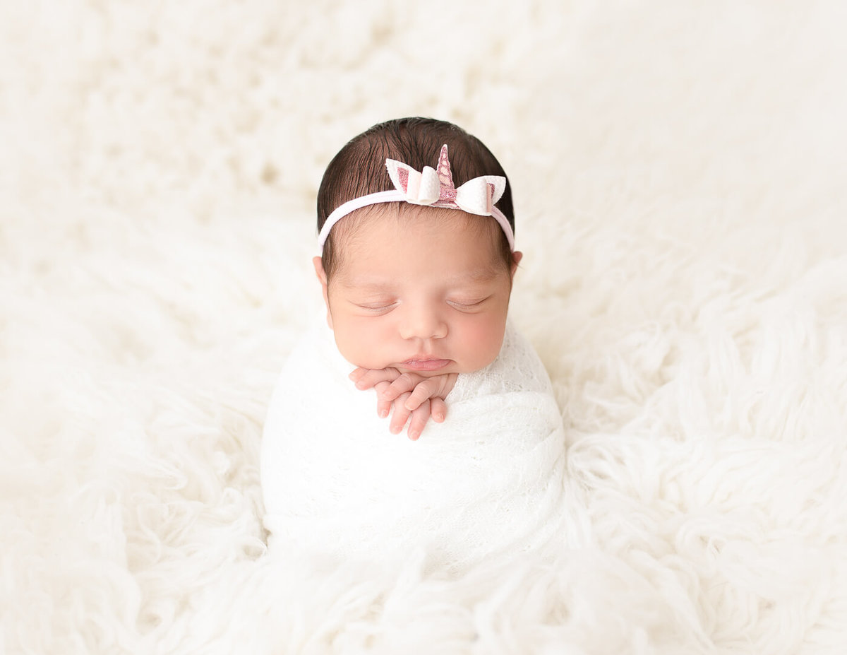 Posed newborn girl at our studio in Rochester, Ny.