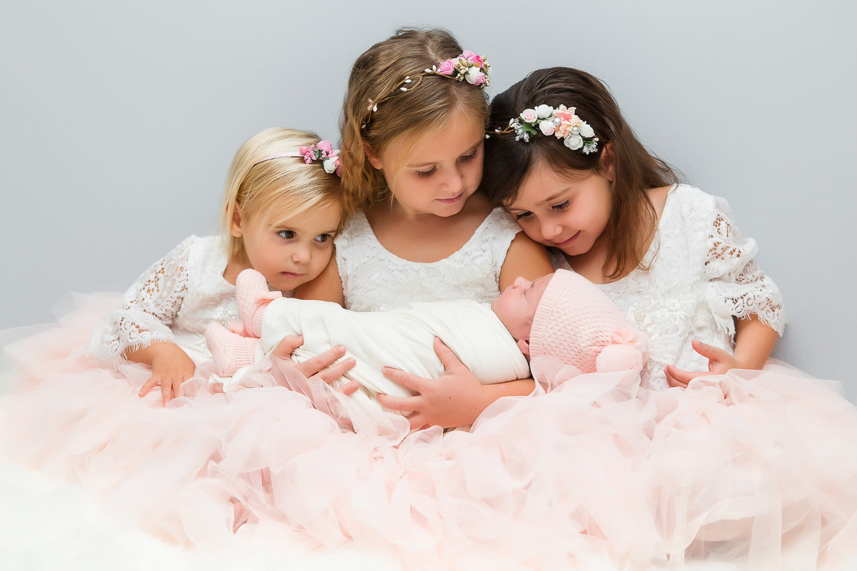 3 sisters in pink tulle dresses looking down at newborn baby girl {Oakville Lifestyle Photographer}