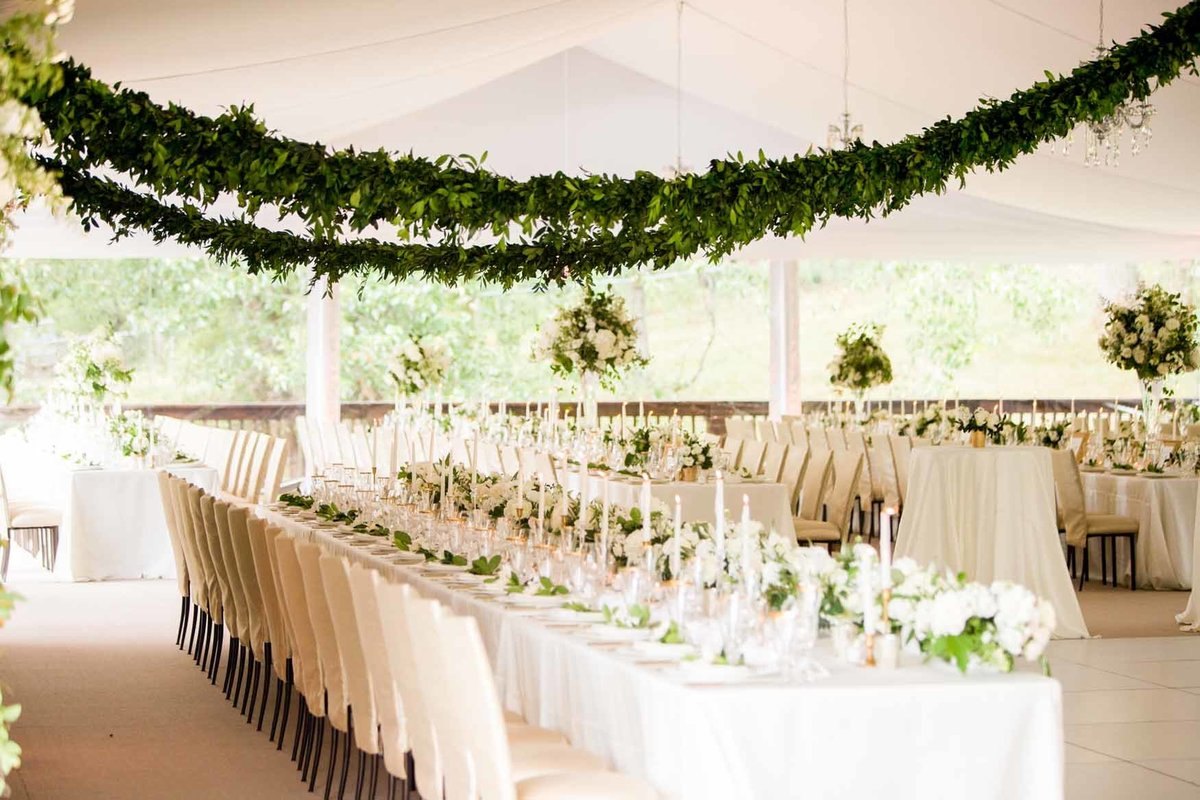 Wedding reception in white tent with long tables and green garlands hanging above