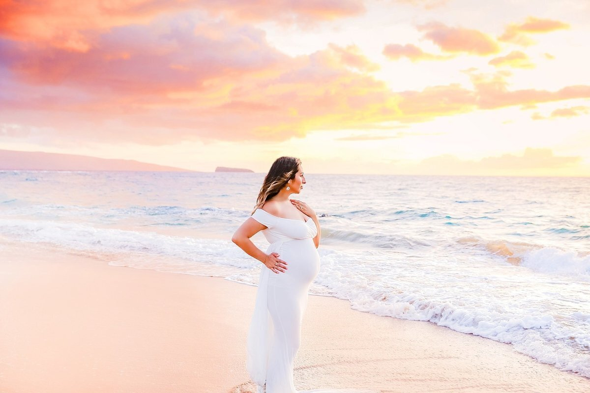 Stunning Maui sunset and pregnant woman wearing white maternity gown for her portrait session in Wailea