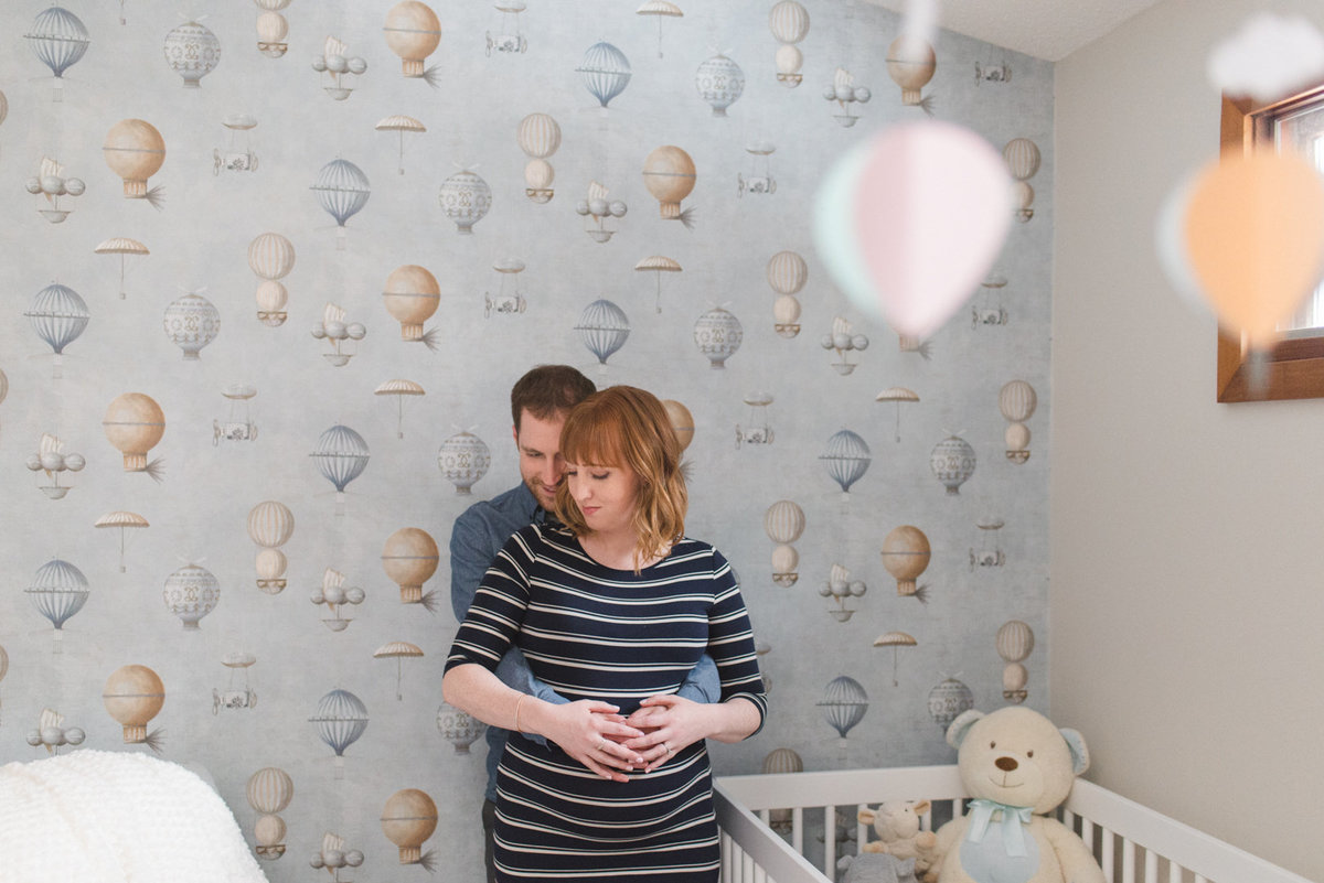 Expecting parents in baby's nursery with hot air balloon wallpaper