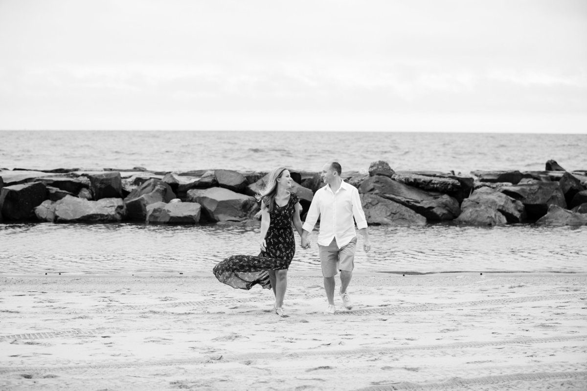 engaged couple walk on beach at asbury park