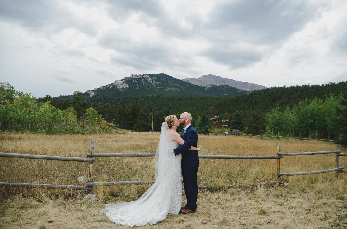 bride and groom kissing infront of rocky mountains