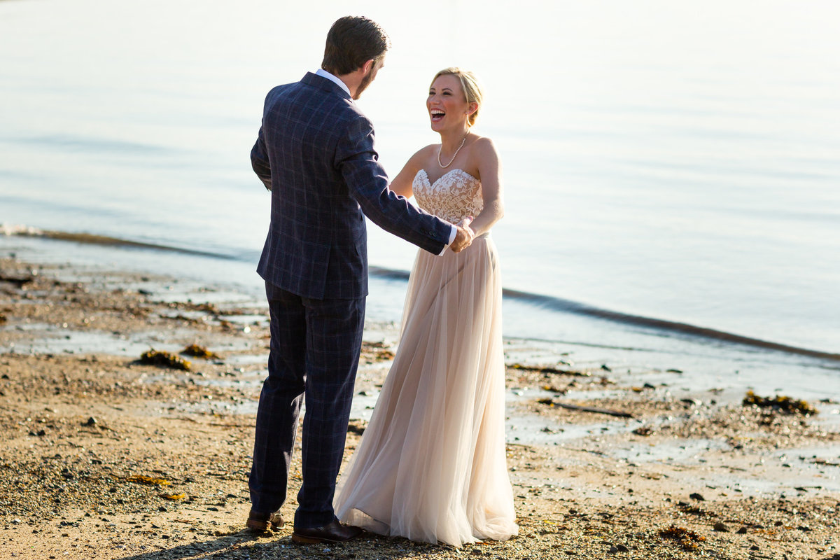 Peaks Island Maine Wedding Photographer with the newlyweds dancing by the ocean on the beach after being married along the ocean