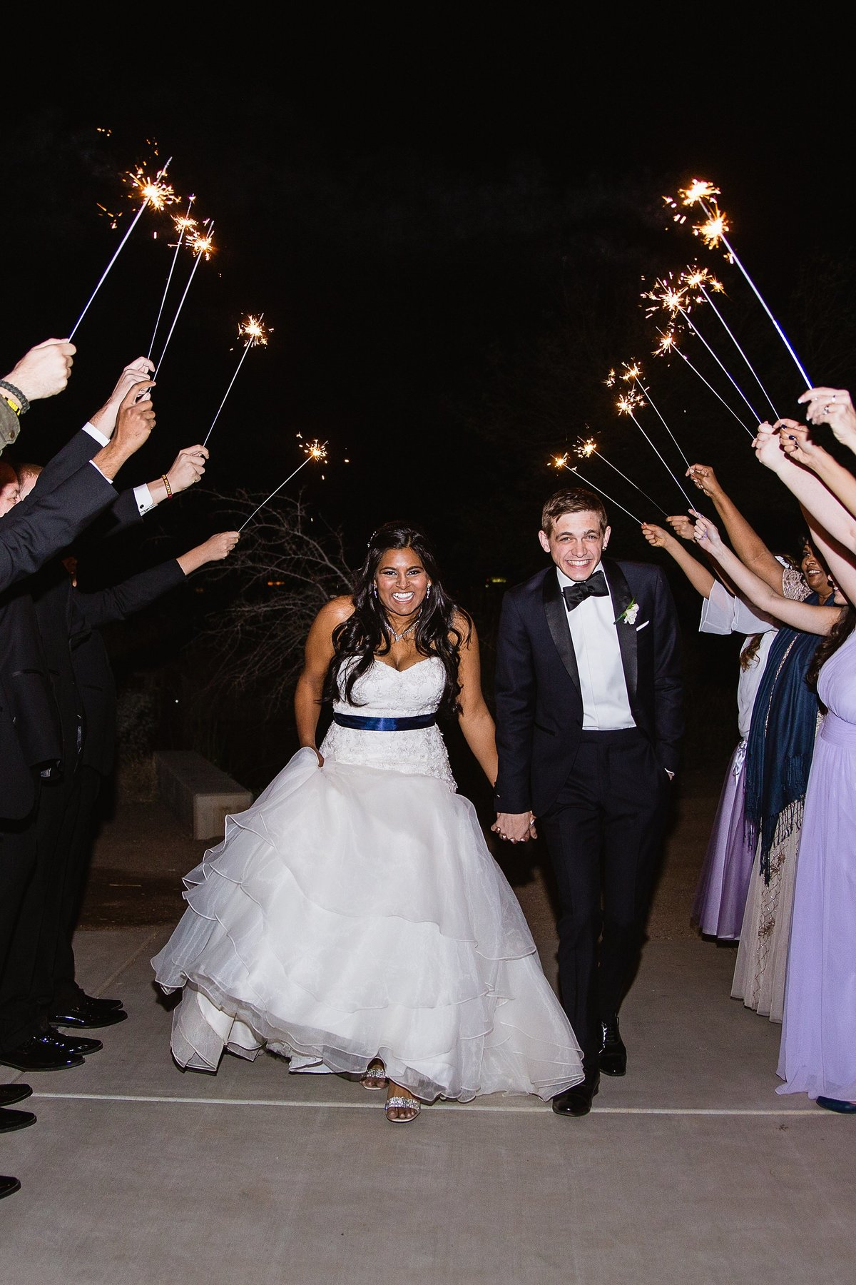 Bride and groom during their sparkler exit by Phoenix wedding photographers PMA Photography.