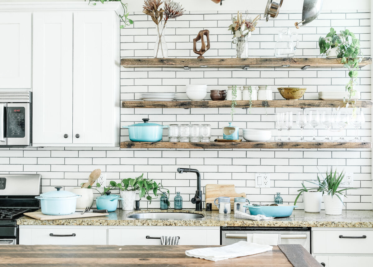 A rustic boho kitchen is tiled with white tiles and grey grout, with a stone marble worktio and natural wood shelves.
