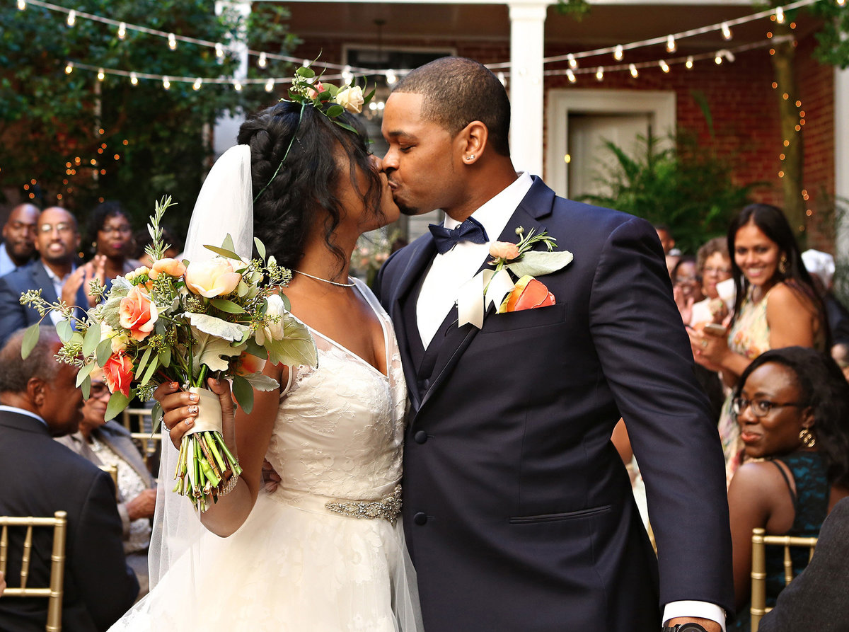 nola bride and groom kiss at back of ceremony in courtyard
