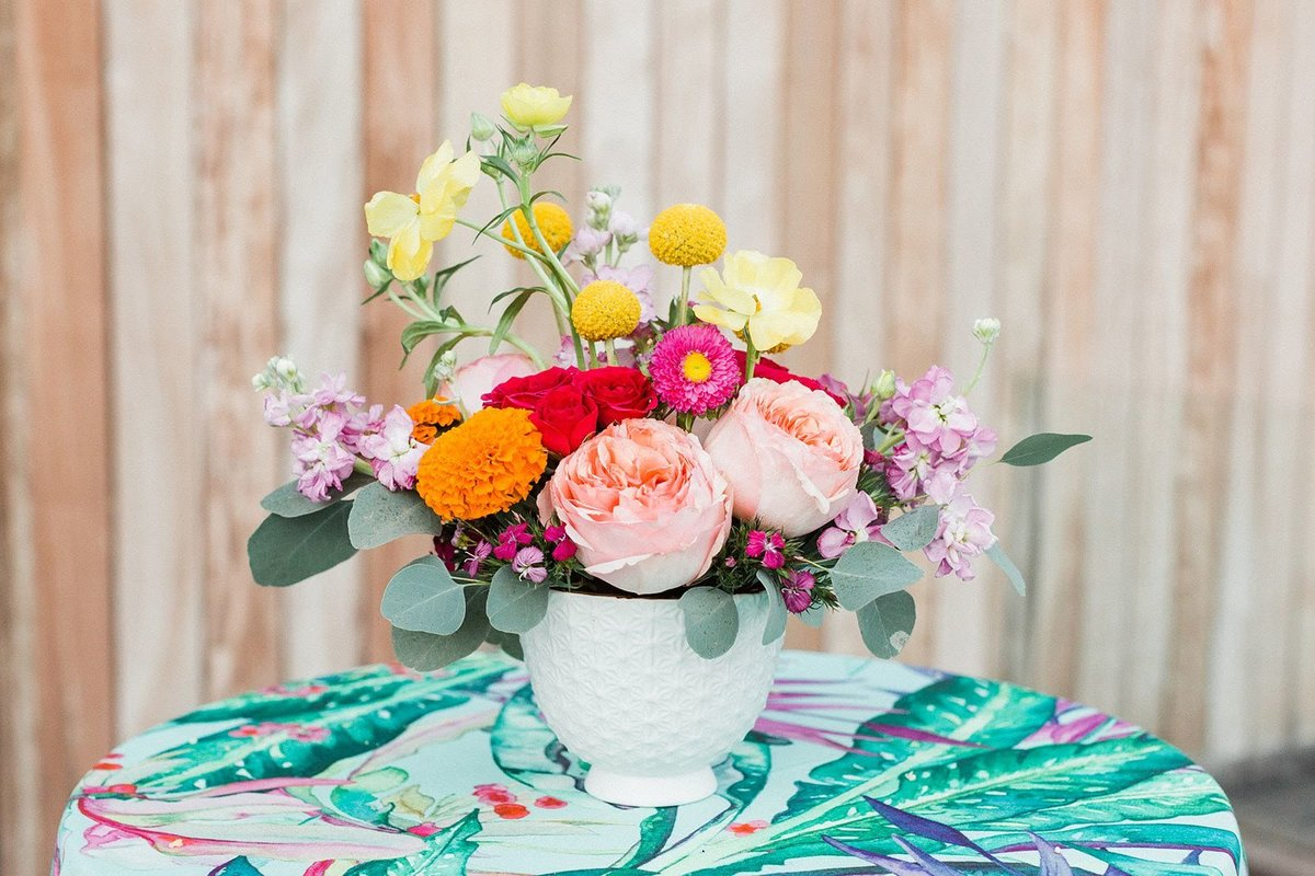 Bright floral centerpiece with tropical linen