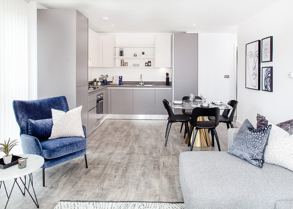 A bright, light modern design is set within an open plan apartment with a grey kitchen and accent blue armchair.