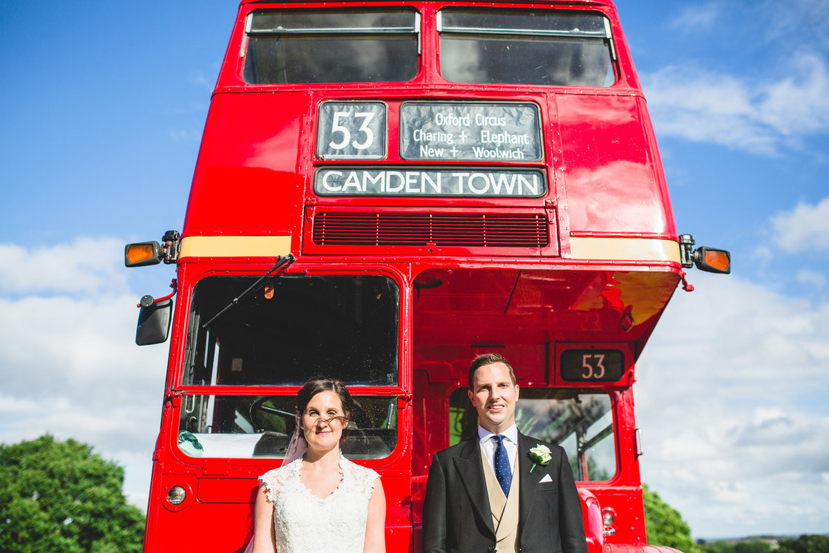 couple in front of a big red bus