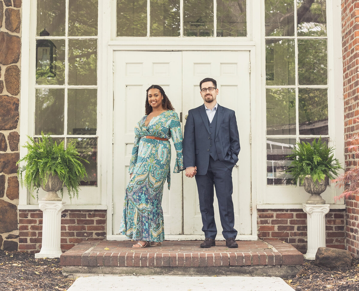 engaged couple standing by doors smithville village, smithville, nj