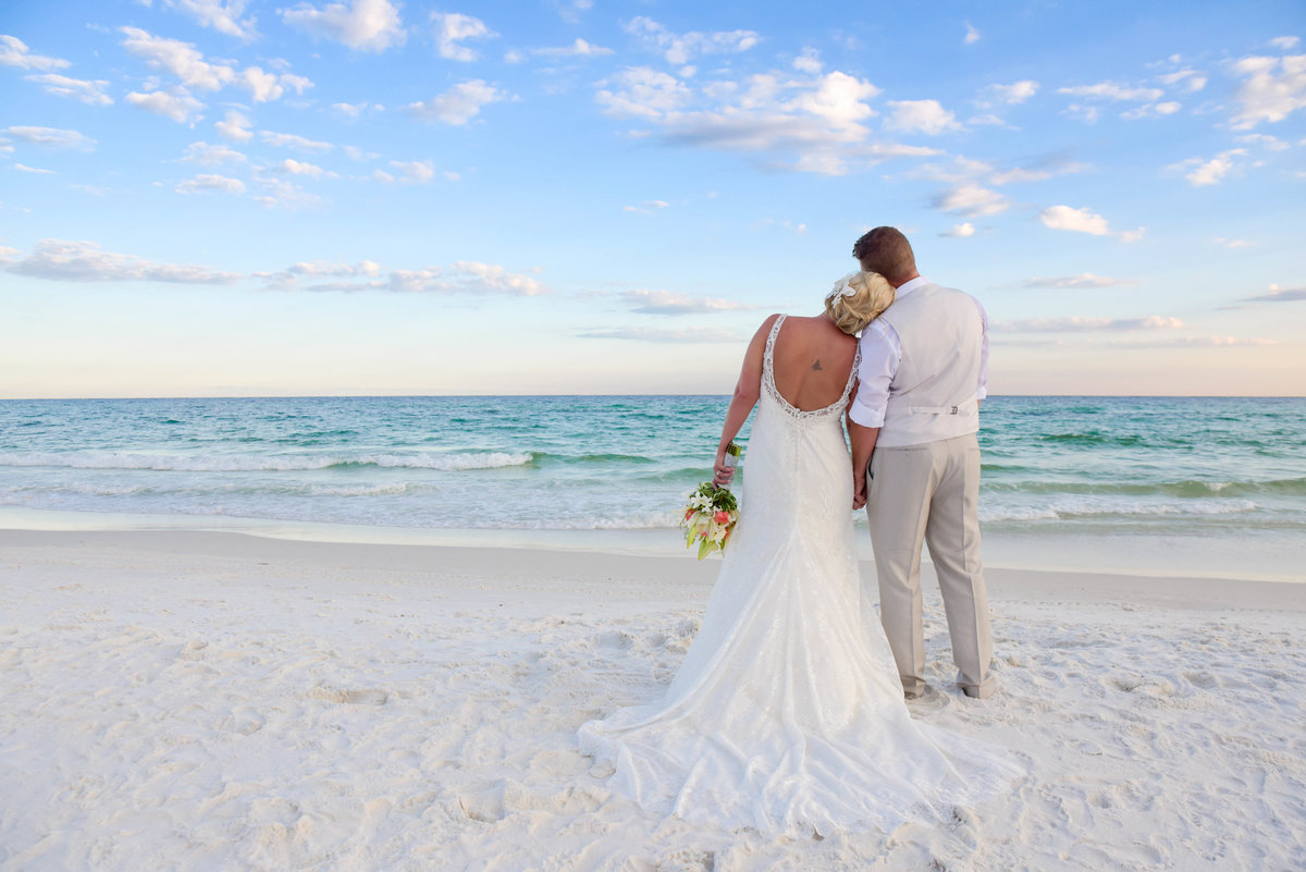 Bride leaning her head on the groom while looking out into the ocean in Fort Walton Beach, FL