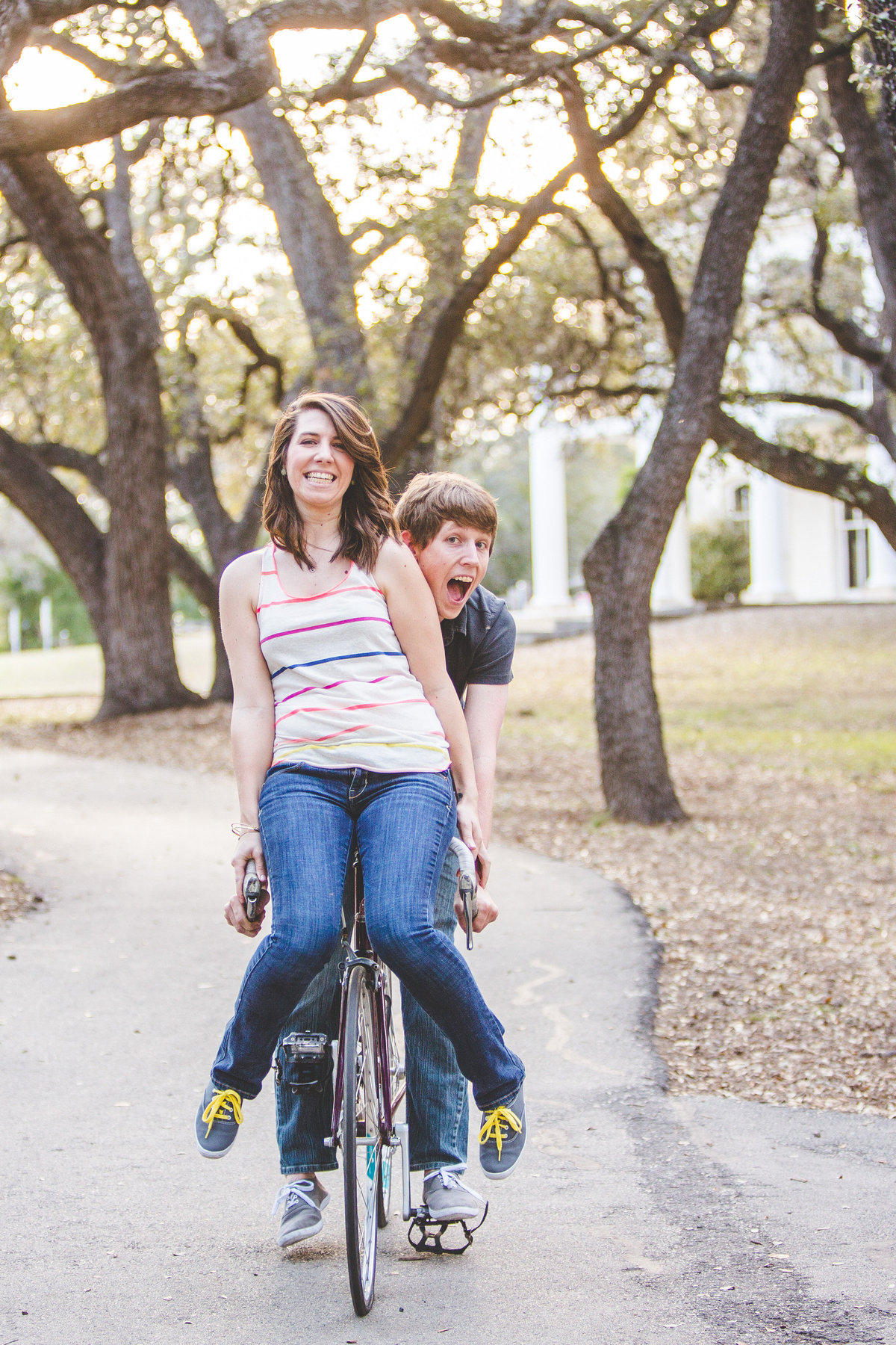 Engaged couple riding one bike together. Fiancée is on the handlebars and fiancé is pedaling at Denman Estate Park in San Antonio.