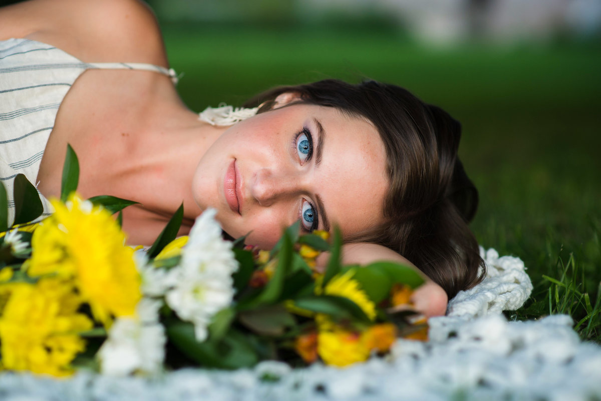 Senior Session Girl with flowers laying in the Grass