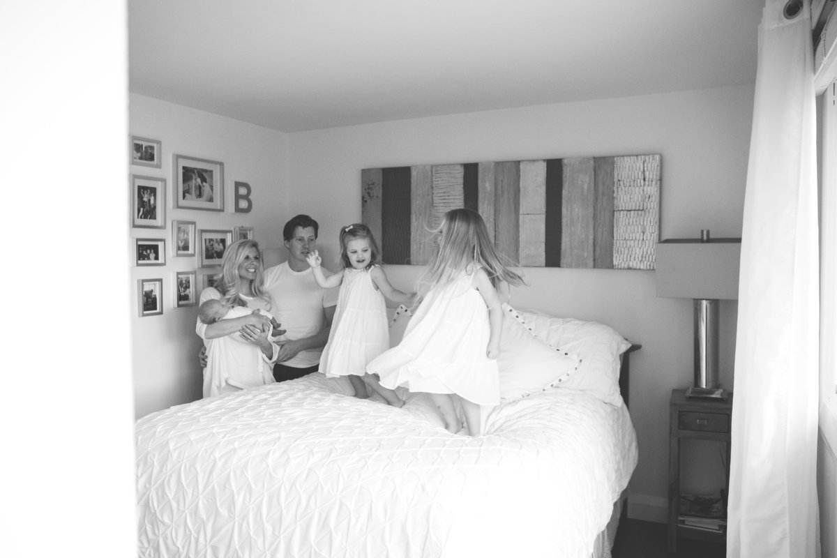 Parents holding newborn, daughters jumping on bed {Oakville Family Photographer}