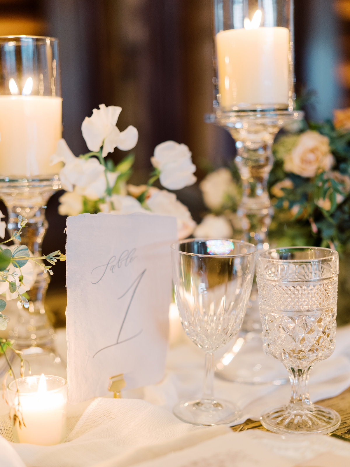 a photo of a handmade table number in calligraphy with crystal clear water goblets and wine glasses at a wedding in Las Vegas at Red Rock Casino