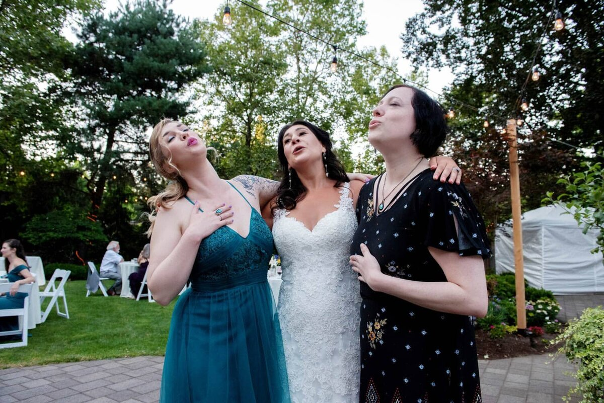a bride and two friends hug and sign along to a Queen song