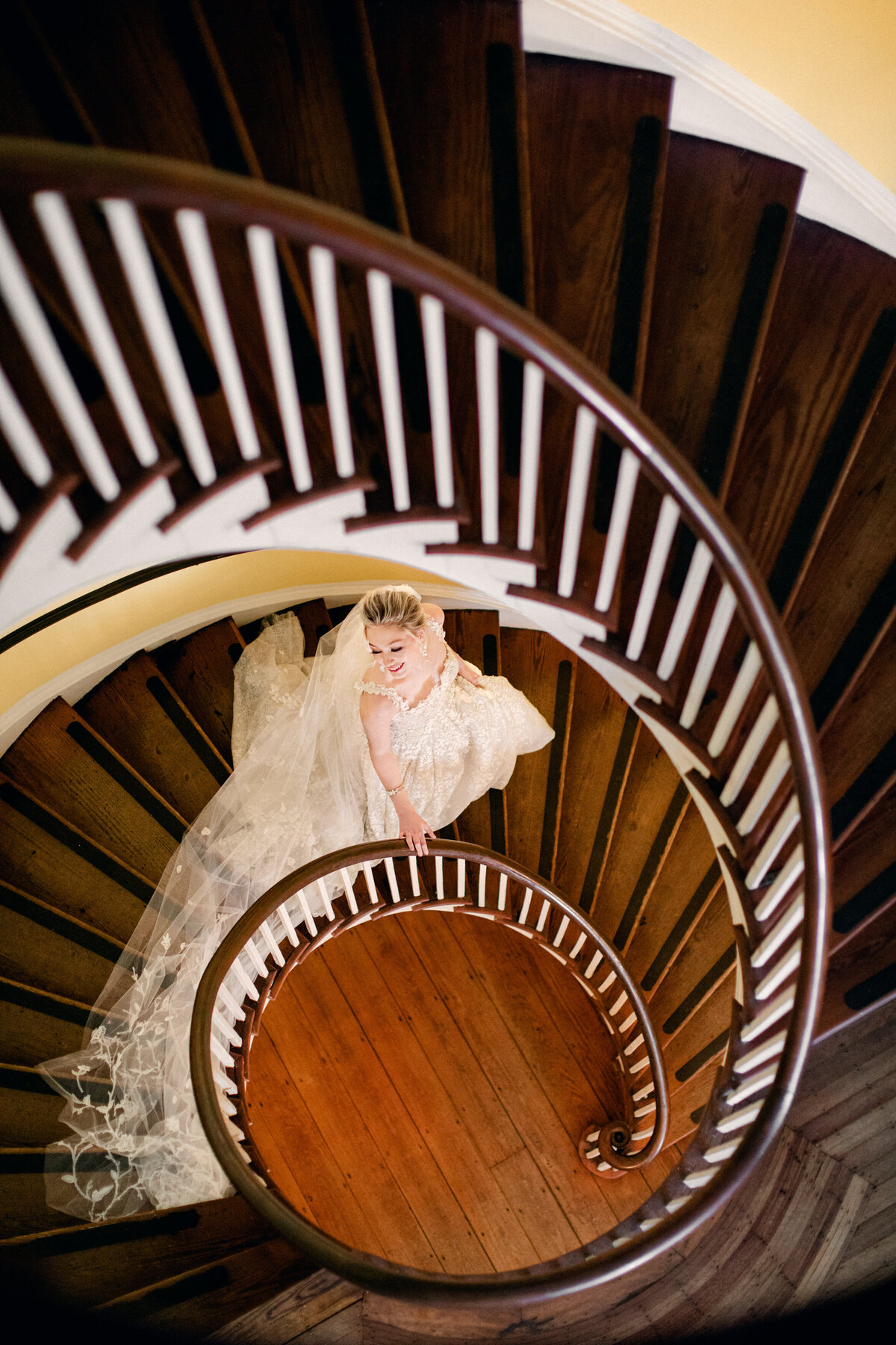 bride walking down spiral staircase in white dress at Lowndes Grove Charleston Wedding