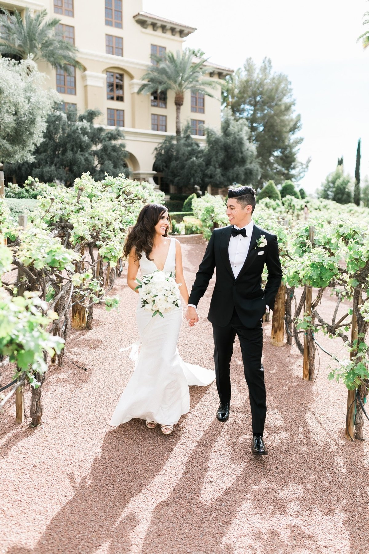 a photo of a bride and groom walking through a vineyard at their wedding at Green Valley Ranch Resort and Spa in Las Vegas