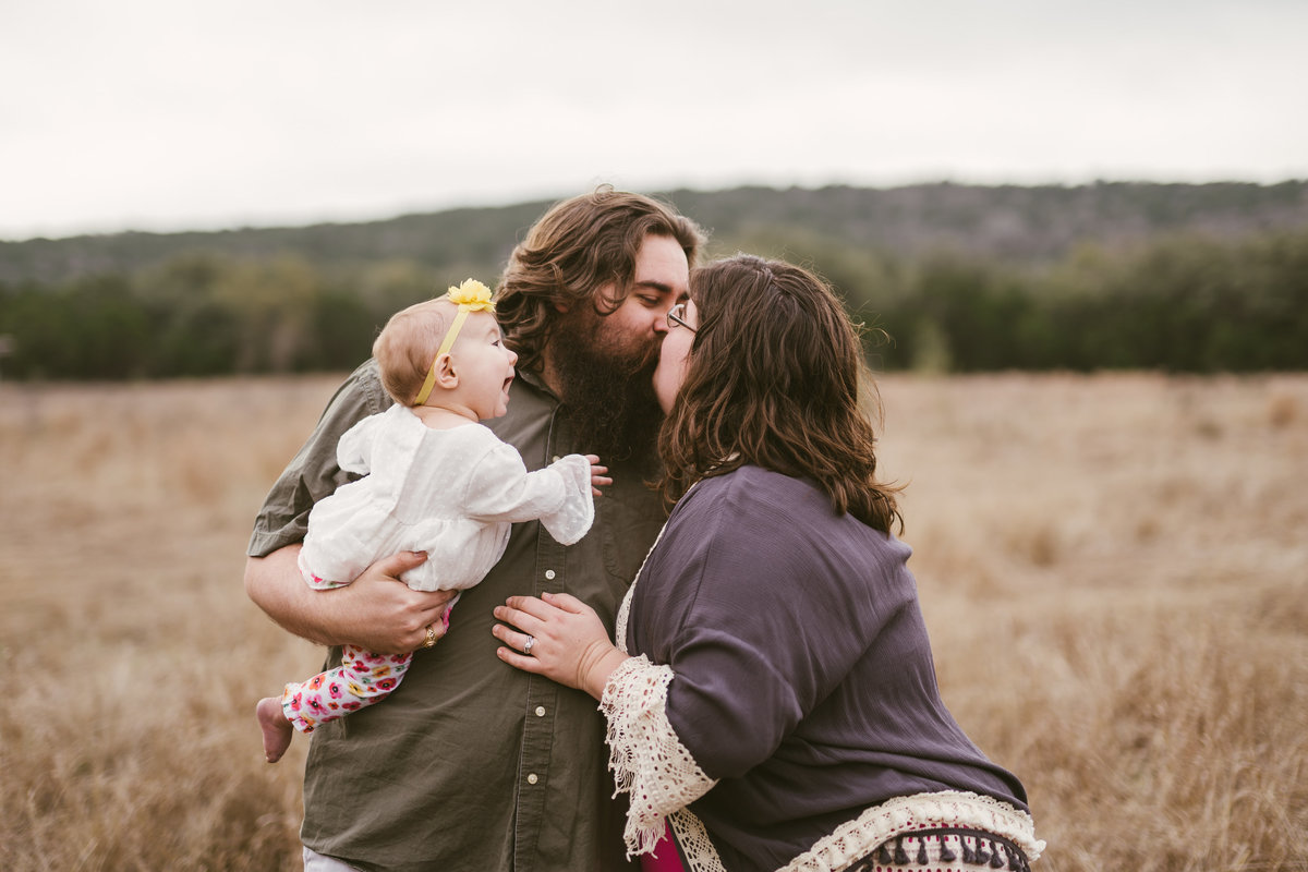 family portrait session mom and dad kissing and dad holding baby by San Antonio photographer