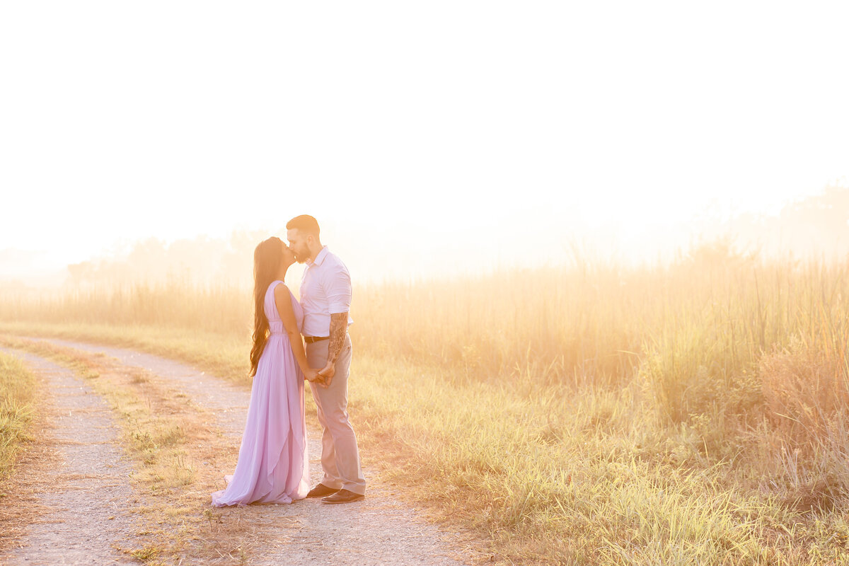 Summer Sunset Romantic Engagement Session couple kissing in lavender maxi dress in field on dirt road at Busch Wildlife in St. Louis by Amy Britton Photography Photographer in St. Louis