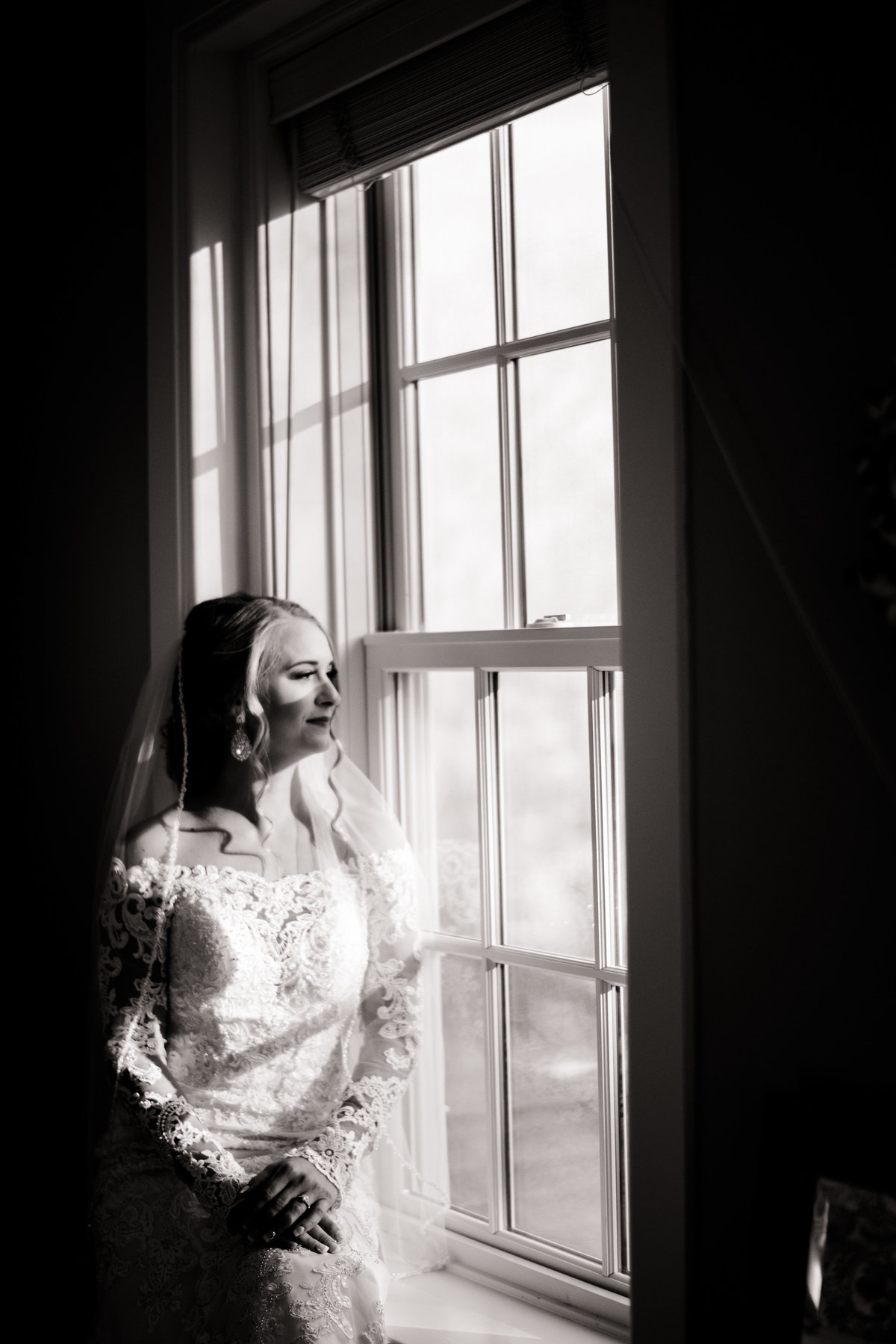 black and white image of bride by window