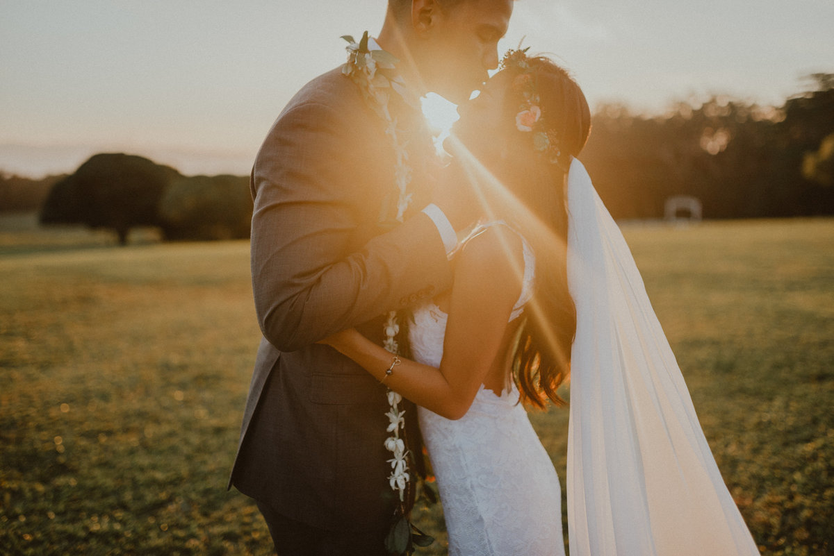 groom gently holds bride's face while the suns shines between them at golden hour and bride's veil moves in the wind