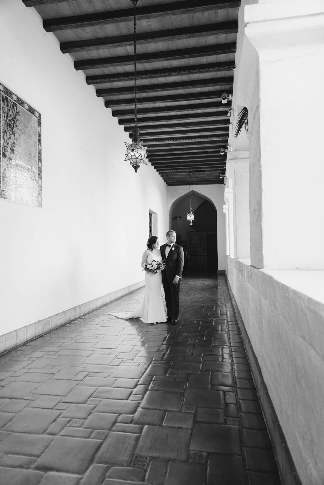 A bride and groom look to the side while standing in a hallway with stone floors and white painted walls