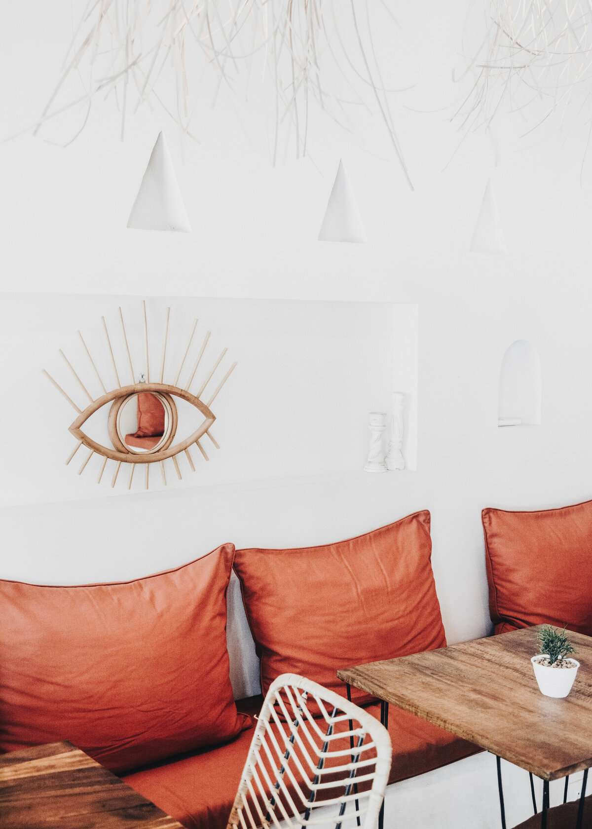 A restaurant has been designed with a boho style with terracotta cushions and an eye shaped mirror.