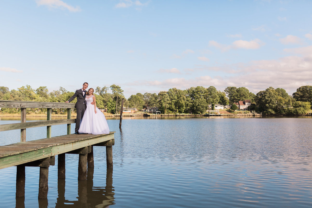 A bride and groom stand on the dock at Fort Eustis