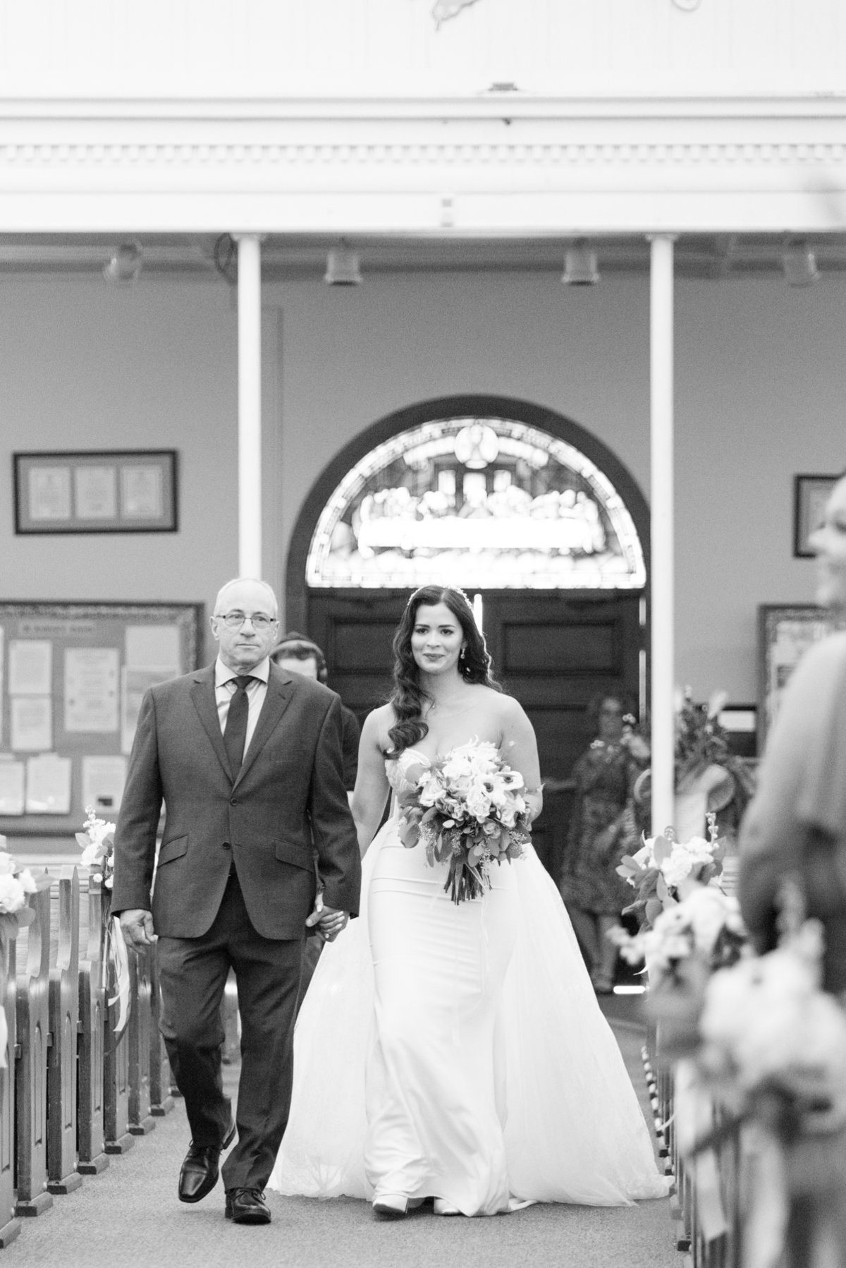 Bride walking down the aisle of St. Andrews Church in Thundr Bay