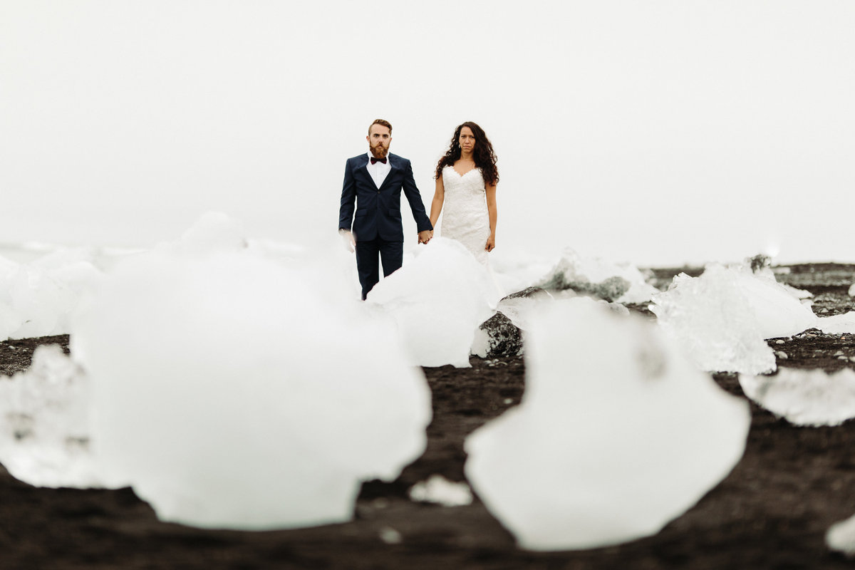 Bride & groom pose in the ice formations on the black sand beach  after their Iceland wedding.