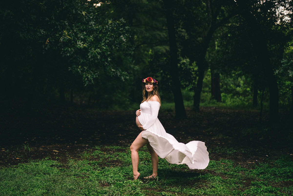Maternity session of woman wearing flower crown and white flowing dress at Denman Estate Park in San Antonio.