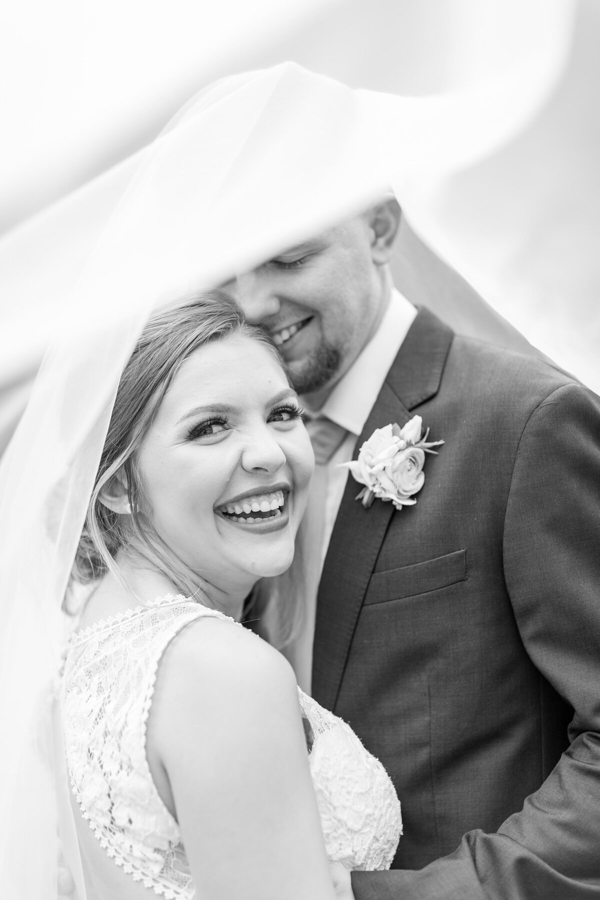 Black and White Photo of Bride and Groom Under the Veil