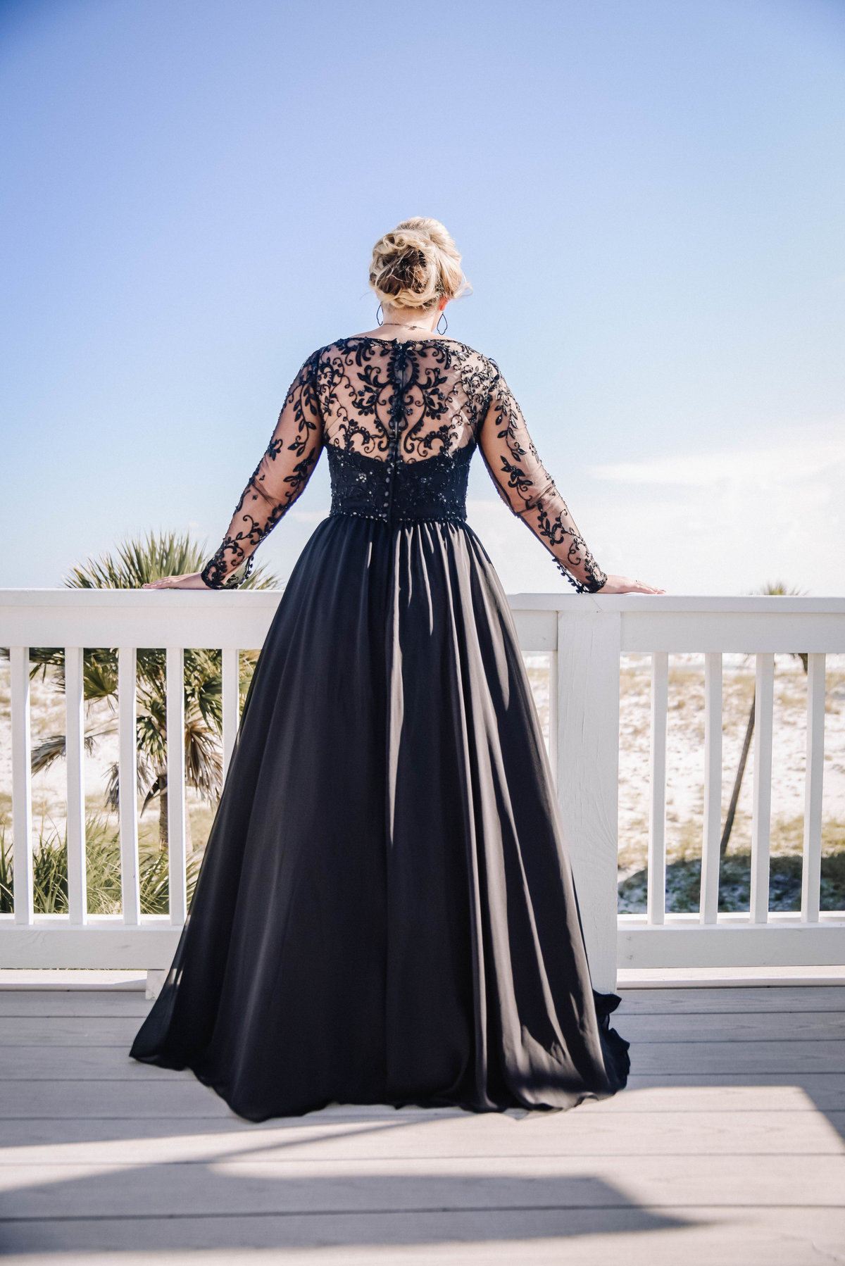 Bride in a black wedding dress looking  out on Pensacola beach.