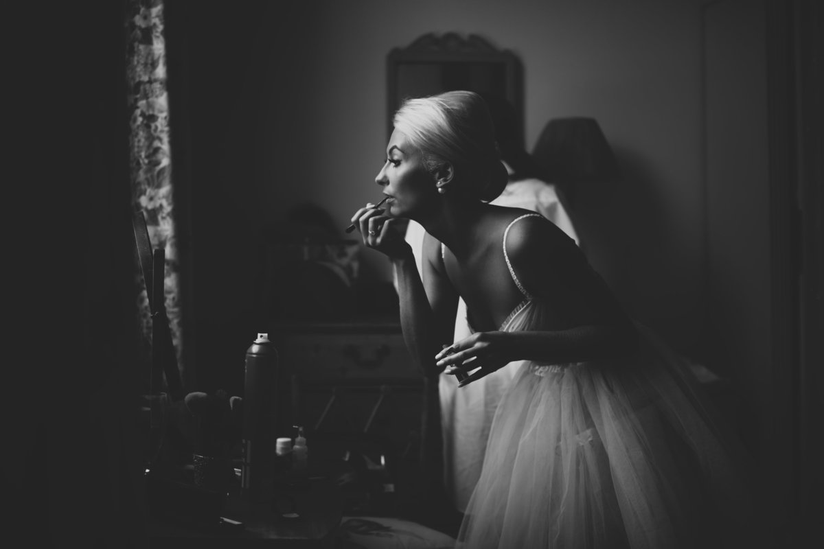 black and white photo of bride doing makeup in front of a window. bride is wearing a rara skirt