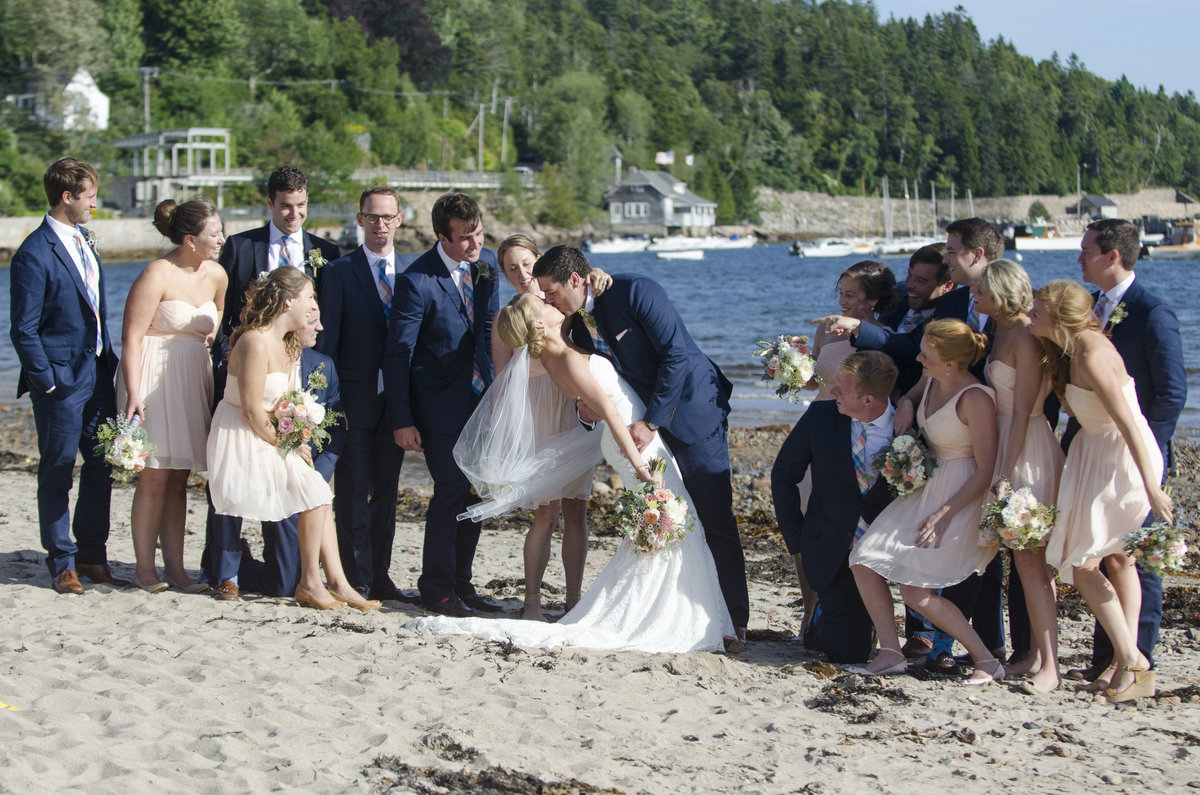 Groom dips bride for a kiss on the beach in Portland, Maine as bridal party looks on & smiles